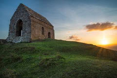 Romantic sunset on Cornish coast with lonelly chapel on cliff. Royalty Free Stock Photography