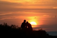 Romantic Sunset. Couple watching the sun set over the Mediterranean from Menorca. Young lovers enjoying a tranquil moment Royalty Free Stock Photography