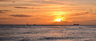 Romantic Sunset in Hawaii. A yellow sunset with a warm glow, the sun is behind the clouds and sailor boat at the horizon Stock Photo