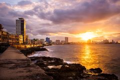 Romantic sunset at the Malecon seawall in Havana. With a view of the sea and the waterfront buildings Stock Photos