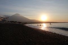 Romantic sunset on the sea coast in Indonesia. Surfer goes to enjoy paddleboard at sunset.Coastline panorama with majestic volcano stock photos