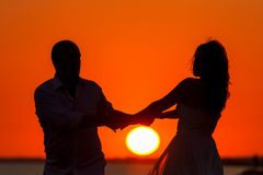 Romantic sunset and silhouettes of lovers royalty free stock photography