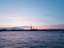 Romantic sunset in St. Petersburg during the white nights. Purple sky, clouds, waves and ships on the Neva. Silhouette of fortness Royalty Free Stock Image