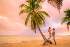 Romantic sunset stroll young couple in love embracing on palm trees at pink dusk clouds sky. Romance on summer travel. Vacation stock image