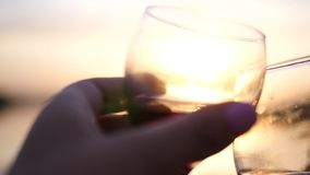 Romantic sunset and two clinking glasses with wine. slow motion. stock footage