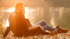 Romantic sunset. Young couple sitting near lake  having good time sunset Royalty Free Stock Images