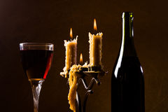 Romantic supper. Wine bottle wineglass candles fire candlestick beeswax black Stock Photography