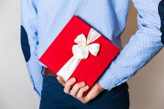 Valentines day gift,handsome Young man hiding surprise gift behing his back royalty free stock images