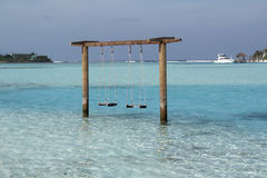 Romantic swing straight into the turquise ocean water in  beach Stock Photos
