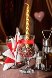 Romantic table decoration - golden candle in a glass with coffee seeds on the table royalty free stock photography