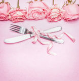 Romantic table place setting with pink roses flowers, cutlery and ribbon. Wedding, invitation , date or greeting card Royalty Free Stock Photography