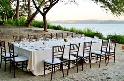 A romantic table set for dinner on the beach Stock Photos