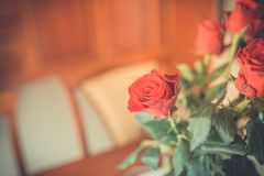 Red roses on table top in vintage style and colors Stock Photo