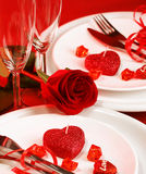 Romantic table setting. Picture of beautiful romantic table setting, luxury white plates served with silverware and glasses for wine and decorated with red rose Royalty Free Stock Images