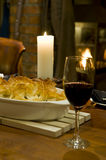 Romantic table setting. A romantic table setting with candle and fireplace in the background, with a gourmet chicken pie and glass of red wine on a beautiful Royalty Free Stock Photography