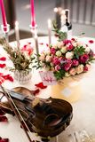 Romantic table setting with beautiful flowers in box, rose petals and violin