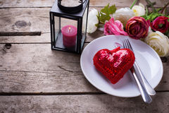 Romantic table setting.  Decorative red heart, knife and fork on white plate Stock Images