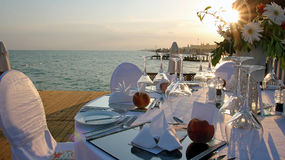 Romantic Table Setting on Pier at Sunset Stock Images