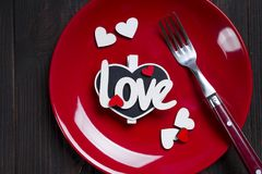 Romantic table setting for Valentines day. Close up table setting for Valentines day with letter Love on dark wooden background, flat lay copy space Stock Images