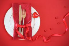 Valentines day table setting with white plate fork and knife shape heart on red tablecloth with ribbon bow background. Romantic. Romantic table setting for stock photos