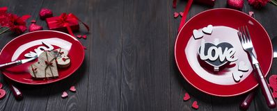 Romantic table setting for Valentines day. With letter Love on dark wooden background, flat lay copy space Stock Photos