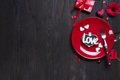 Romantic table setting for Valentines day. With letter Love on dark wooden background, flat lay copy space Royalty Free Stock Photography