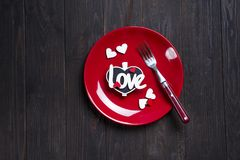 Romantic table setting for Valentines day or wedding. With letter Love on dark wooden background, flat lay copy space Stock Photos
