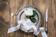 Romantic table setting with white rose as decor, vintage dishware, silverware and decorations on wooden board. Royalty Free Stock Photos