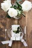 Romantic table setting with white rose as decor, vintage dishware, silverware and decorations on wooden board. Stock Image