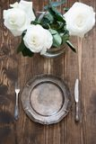 Romantic table setting with white rose, vintage dishware, silverware and decorations on wooden board. Selective focus. Royalty Free Stock Photo
