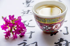 Romantic tea. Tea cup and pink flower over background with oriental symbols royalty free stock photo