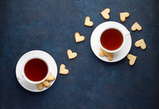 Romantic tea party for lovers on Valentines day. Sweet heart shaped cookies with two cups of tea on stone background. Top view, copy space royalty free stock images