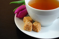 Romantic Tea Time. A cup of tea with cubes of brown sugar and a pink tulip on a plate Royalty Free Stock Photos