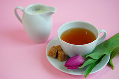Romantic Tea Time. A cup of tea with cubes of brown sugar and a pink tulip on a plate with the jug of mil on the side Stock Photo