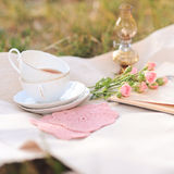 Romantic tea time outdoors. Cup of tea, open book, lamp, roses on cover outdoors Royalty Free Stock Images