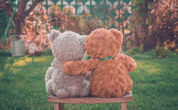 Romantic Teddy bears couple. Teddy bears on the bench in the garden. Tenderness and romance Royalty Free Stock Images