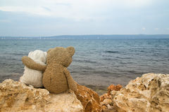 Romantic teddy bears. Two romantic teddy bears sitting on the rock by the sea Royalty Free Stock Photo