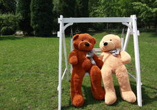 Romantic teddy-bears. Two teddy-bears sitting on swing Royalty Free Stock Images