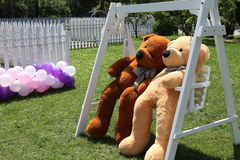 Romantic teddy-bears. Two teddy-bears sitting on swing Stock Photography