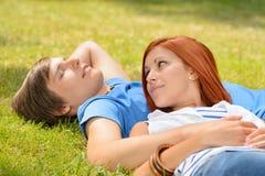 Romantic teenage couple lying on grass summer Stock Photo