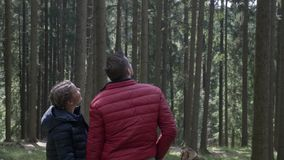 Romantic teenage couple relaxing in vacation trip pointing and looking at nature in a beautiful mountain woods forest landscape stock video footage