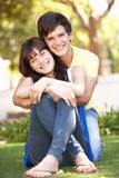 Romantic Teenage Couple Sitting In Park Stock Image