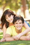 Romantic Teenage Couple Sitting In Park Stock Photo