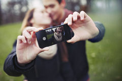 Romantic teenage couple taking self portrait. With cell phone at the park. Young men and women in love. Asian male and female model Royalty Free Stock Photography