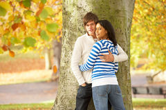 Romantic Teenage Couple By Tree In Autumn Park. Looking at camera Royalty Free Stock Photos