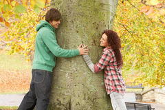 Romantic Teenage Couple By Tree In Autumn Park. Smiling at each other Stock Photography