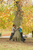 Romantic Teenage Couple By Tree In Autumn Park. Smiling at each other Royalty Free Stock Images