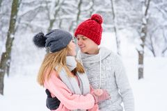 Couple in love looking at each other during snowfall royalty free stock photos