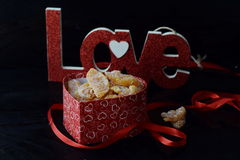 Romantic theme. Box with candied orange slices, Love sign on black abstract background. St. Valentine`s day. royalty free stock photo