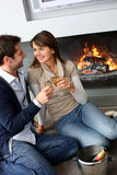 Romantic time. Cheerful couple drinking champaign by fireplace Stock Photography